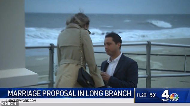 NBC New York reporter Brian Thompson was completing a weather segment at the Jersey Shore when camera's captured a engagement in real time (pictured)