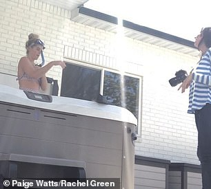Laughing: As Paige poses in a backyard hot tub with flippers, she is seen laughing at the ridiculousness of it