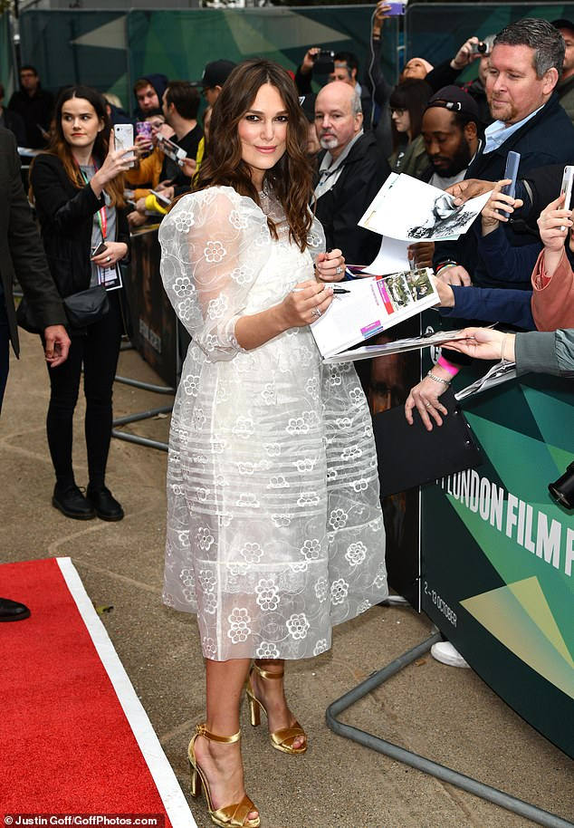 Standing tall: Boosting her height in a pair of glamorous gold peep-toe heels, Keira looked happy and relaxed as she signed fan autographs and posed for snaps