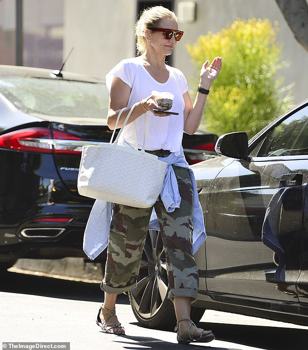 On the move: The 47-year-old teamed a simple white T-shirt with a pair of camouflage trousers, jazzing up the look with a chic white Goyard handbag