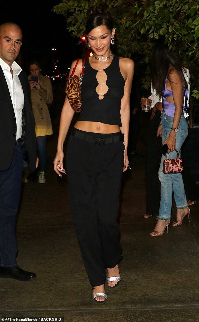 Party time: Bella dared to bare for her big night, going braless in a skimpy black top and baggy black pants