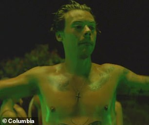 Ink job: The singer showed off his many tattoos as he went topless for the party scenes