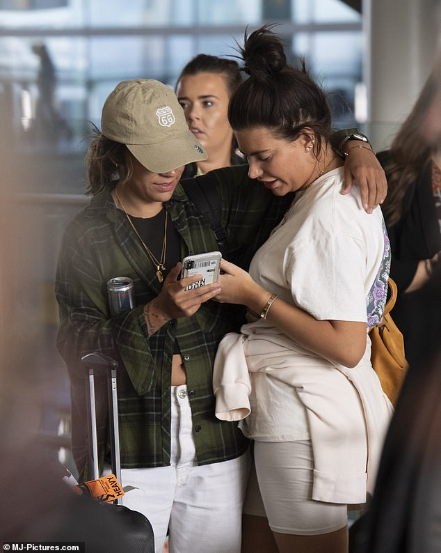 Helping hand: Fulham Ladies footballer Chelcee, 27, put a loving arm around Megan as they waited for their ride home from the airport
