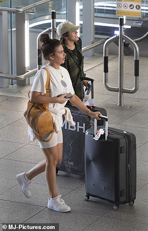 Heading home: The couple took a suitcase each as they made their way through the airport