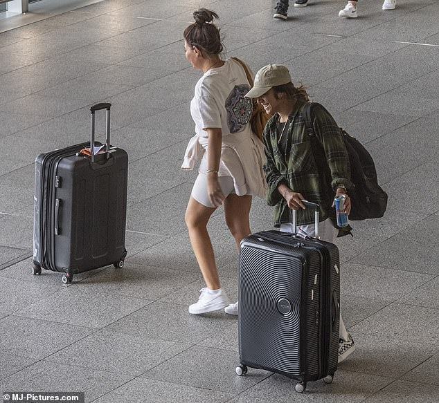 Relaxed: The couple laughed as they pushed their suitcases out of the airport terminal