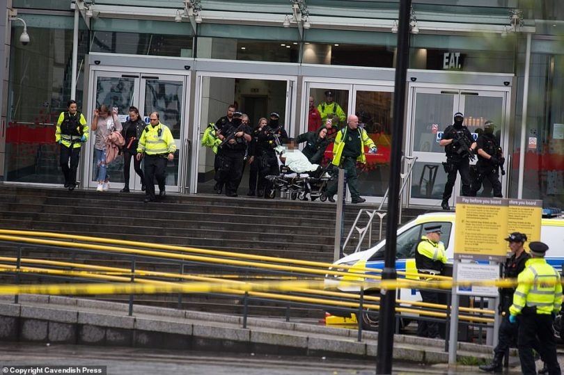 Another woman was among the victims wheeled away surrounded by armed police at around midday today