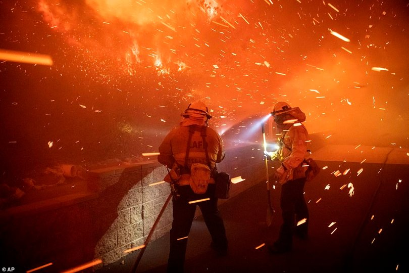 The fire broke out along the 210 Freeway near Yarnell Street and jumped the highway. Pictured: Embers from the Saddleridge fire blow by firefighters in Sylmar on Thursday