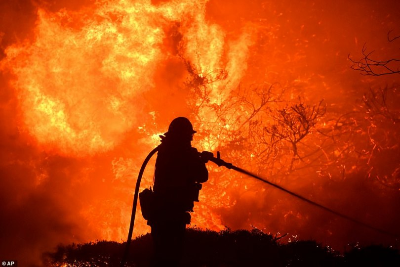 A firefighter battles the Saddleridge fire after it began in Sylmar, California, after 9pm on Thursday