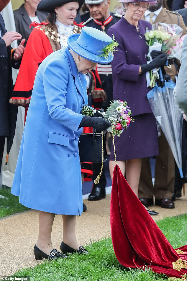 Queen Elizabeth II unveils a plaque at the Haig Housing Trust to officially open their new housing development in Morden