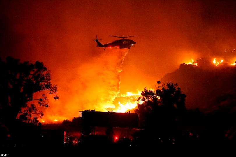 Water is dropped by helicopter on a large brush fire in Sylmar, California, on Friday morning