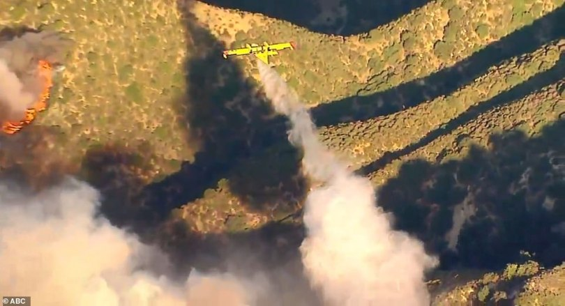 Helicopters made repeated water drops as 1,000 firefighters on the ground attacked flames in and around homes. Pictured: Water fighter planes dumped gallons on the still-burning Saddleridge Fire on Friday morning