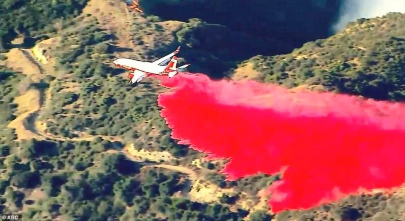 A plane dropped a red retardant, a substance used to slow or stop the spread of fire or reduce its intensity, over Sylmar, where the Saddleridge Fire began, on Friday morning