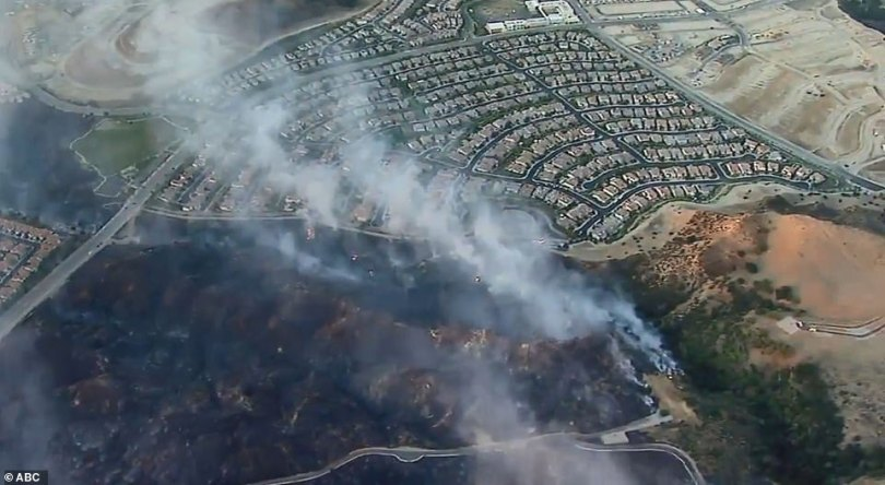 More than 4,000 acres burned overnight and more than 12,000 homes were under mandatory evacuation. Pictured: Smoke over Sylmar on Friday morning