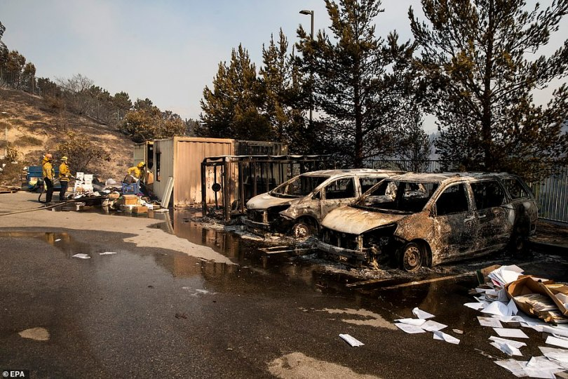 irefighters work to extinguish the Saddleridge Fire on a parking lot next to two burnt cars in Porter Ranch on Friday