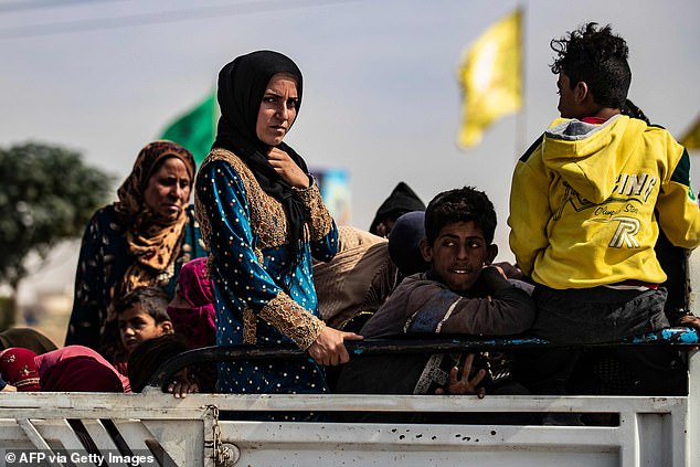 Displaced Syrians sit in the back of a pick up truck as Arab and Kurdish civilians flee amid Turkey's military assault on Kurdish-controlled areas in northeastern Syria