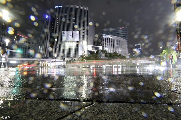 Cars pass by at Ginza shopping district in the pouring rain due to Typhoon Hagibis in Tokyo