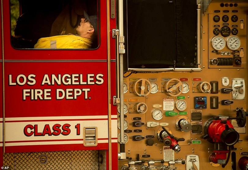 A firefighter rests as crews continue to battle the Saddleridge Fire in Porter Ranch