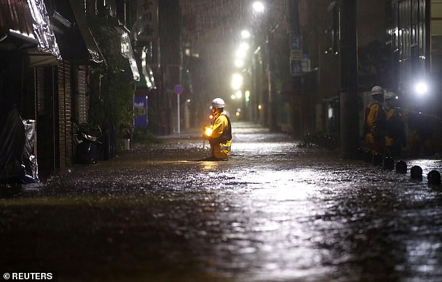 Firefighters patrol on a flooded road due to heavy rains caused by Typhoon Hagibis at Ota ward in Tokyo