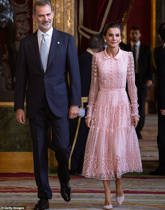 Queen Letizia of Spain attends a reception at the Royal Palace with King Felipe (left) who wore a smart suit for the occasion