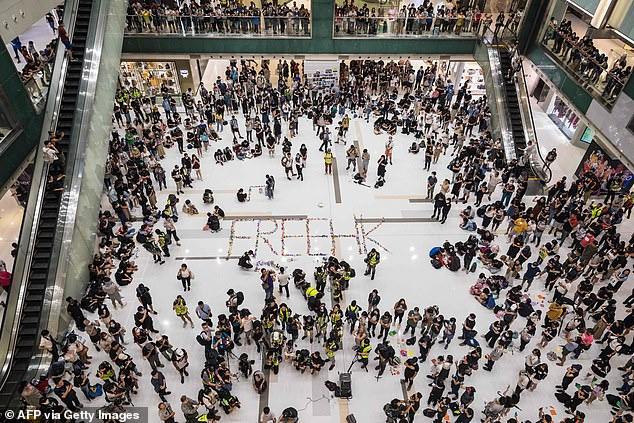Around 300 people gathered for a rally at a shopping mall in the Sha Tin district, writing 'FREEHK' on the white linoleum floor