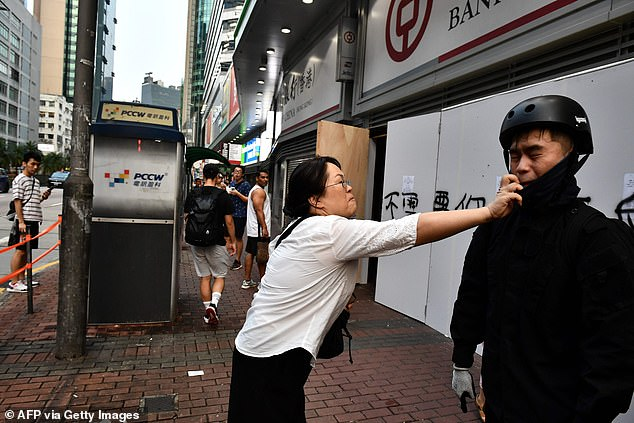 A woman tries to remove a facemask worn by a protesters after an anti-emergency law march from the Tsim Sha Tsui to Sham Shui Po