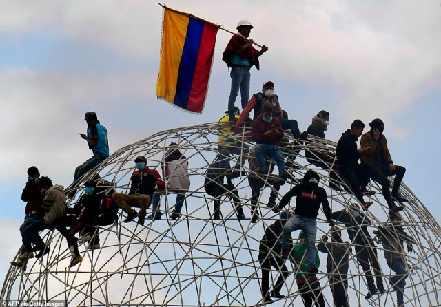 Demonstrators sit atop the sculpture Esfera de Movimientos Oscilantes ('Sphere of Oscillating Movements') at the El Arbolito park in capital Quito during the 10th day of the protest, which was sparked over a fuel price hike ordered by the government to secure an IMF loan