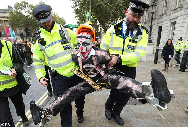 A dossier of files from within XR reveals the inner workings of the protest movement and its finances. One protester is pictured being taken away by police in Westminster, London earlier this week