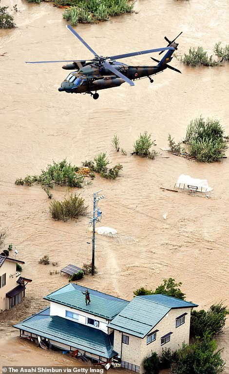 A local resident is rescued from a house submerged in flood water on Sunday