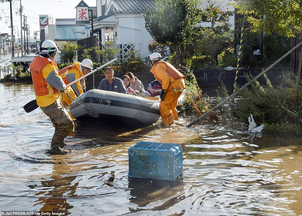 Fire department workers evacuate residents today using a rubber dinghy from a flooded area in Date, Fukushima prefecture
