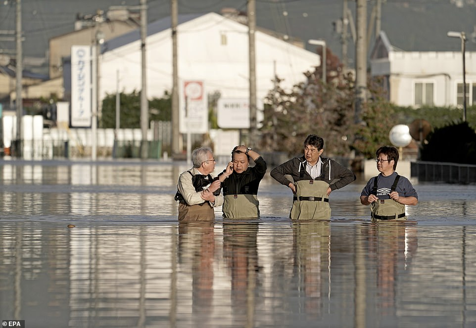 Workers standing waist-deep in flood water check the conditions of their office after the passage of Typhoon Hagibis in Nagano