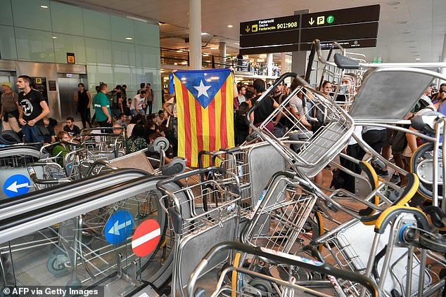 Demonstrators even blocked the escalators of El Prat Airport in Barcelona with luggage trolleys after nine separatist leaders were jailed today over a failed independence bid