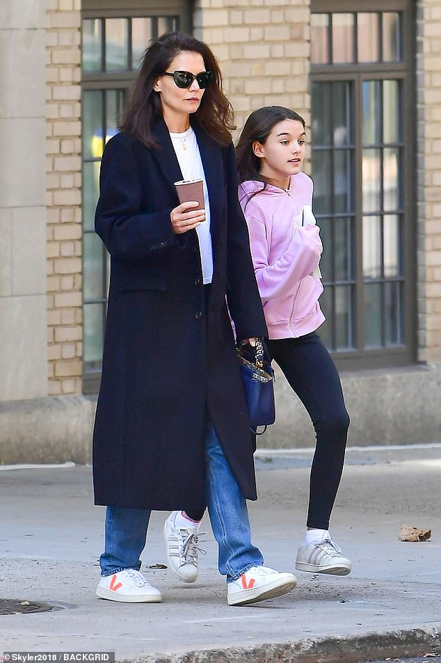 Running errands:Suri Cruise, 13, carried Margaret Atwood's novel The Handmaid's Tale while out with mom Katie while out in New York City on Monday afternoon