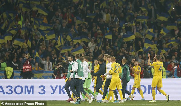 Ukraine's players celebrate their 2-1 victory in the Euro 2020 group B qualifying soccer match between Ukraine and Portugal at the Olympiyskiy stadium in Kyiv, Ukraine, Monday, Oct. 14, 2019. (AP Photo/Efrem Lukatsky)