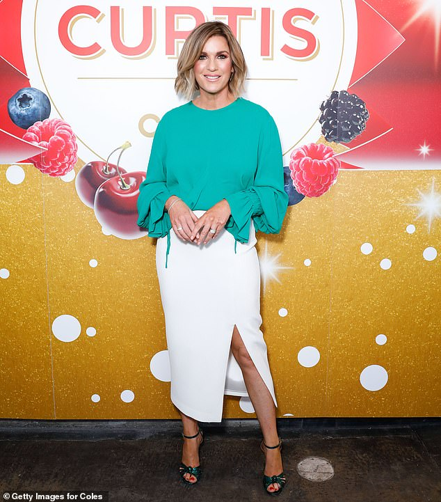 Making them green with envy: Channel Seven's Kylie Gillies, 52, cut a chic figure in a green round-neck blouse tucked into a white skirt with thigh split and metallic green heels