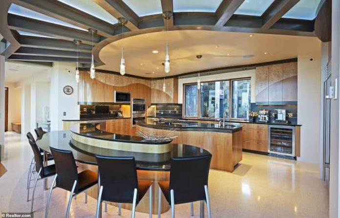 The pad is is bathed in natural light and has walls of glassy windows and marble kitchens