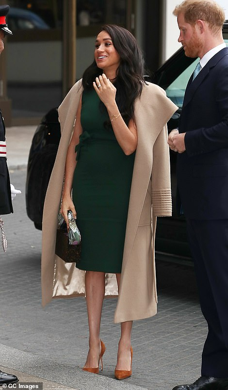 Meghan Markle looked happy to be at the awards as they are greeted on their arrival