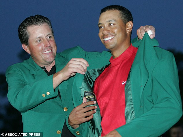 He is presented his green jacket by Phil Mickelson after winning the Masters in 2005