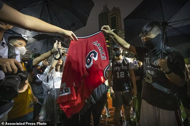 Demonstrators set a Lebron James jersey on fire during a rally in Hong Kong on Tuesday