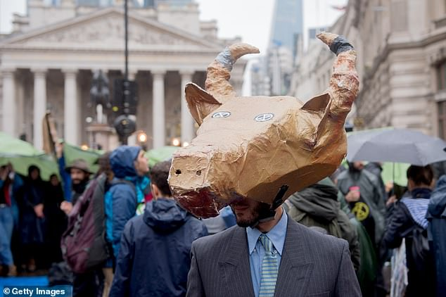 An Animal Rebellion activist is pictured outside the Bank of England on Monday on the seventh day of their 'Autumn Uprising' that has brought chaos to London