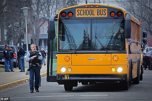 Armed police watch as students from David Worth Dennis School in Richmond, Indiana, are loaded onto a bus after the shooting on December 13, 2018