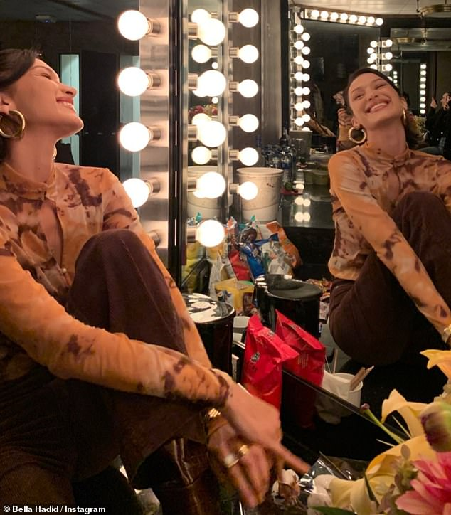 Backstage pass: Bella was beaming in one photo as she struck a pose backstage in the vanity mirror of the dressing room