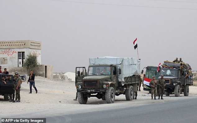 A convoy of military vehicles and busses transporting Syrian regime troops are stationed on the outskirts of the northern Syrian border town of Kobane yesterday