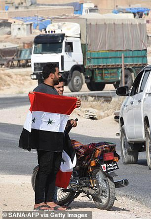 A Syrian man holding a national flag after the Syrian government forces reportedly completed their deployment in the northern city of Manbij