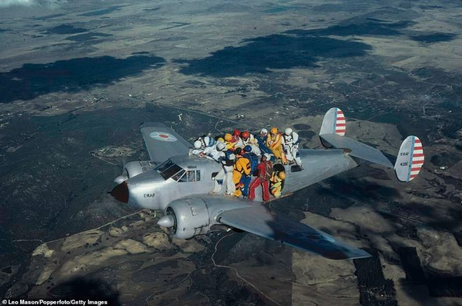 A group of skydivers holding on the exterior of an aeroplane as they prepare to skydive in formation above Lake Elsinore, California, in 1980. Handles had been welded on to the fuselage to help the daredevils hold on. The picture was taken by photographer Leo Mason, who was flying alongside in a Cessna with a door removed