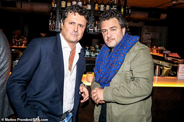 At the bar: Layer and author Enrico Pellegrini posed with a pal who rocked a blue scarf