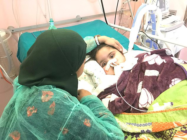 Shelina Begum, 40, (left) said a 'massive weight has been lifted' now her daughter, Tafida Raqeeb (right) is in the care of doctors at Gaslini hospital in Genoa. Miss Begum is pictured keeping a beside vigil after the brain-damaged five-year-old started new treatment