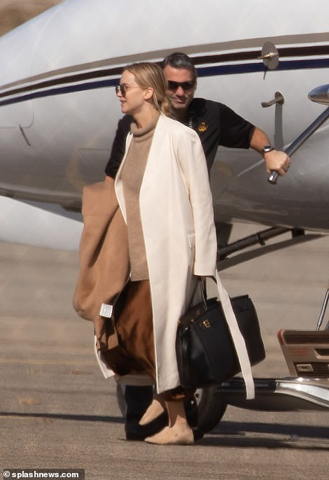 Jennifer stepped off the private plane as a flight crew member dutifully assisted her