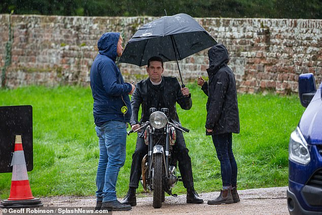 Break time:At one point, the Call The Midwife hunk sat under an umbrella as he took a break from riding around in the rain