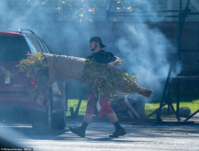 Smoke billowed from the cooking preparations as a worker moved a temporary shrub to block the view of onlookers