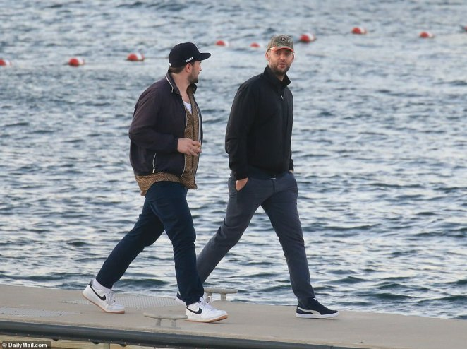Cooke Maroney (right) walks to the ferry landing in black jacket and camo baseball hat